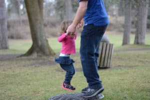 Dad jumping in a boy with his daughter